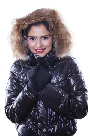 Picture of beautiful indian woman feeling cold and wearing winter jacket, smiling at the camera in the studio