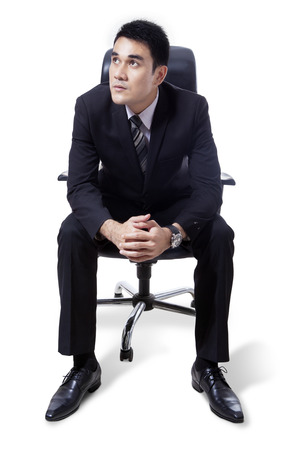 handsome young man: Portrait of handsome businessman sitting on chair and looking up, isolated on white background