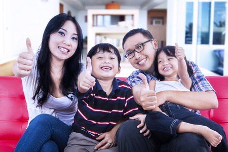 family sofa: Happy family showing thumbs up on red sofa at home