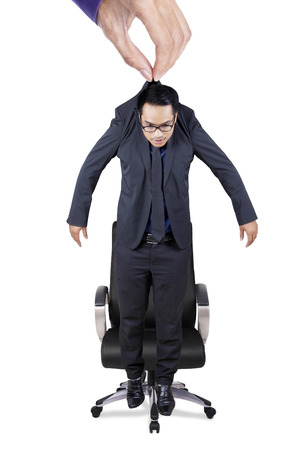Hand lifting a businessman and put him on an office chair, isolated on white background Stock Photo
