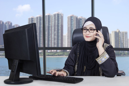 professional woman: Arabian businesswoman working in the office with a computer near the window while talking on the cellphone
