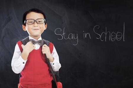 school classroom: Male elementary school student wearing uniform in the classroom with text Stay in School on the blackboard
