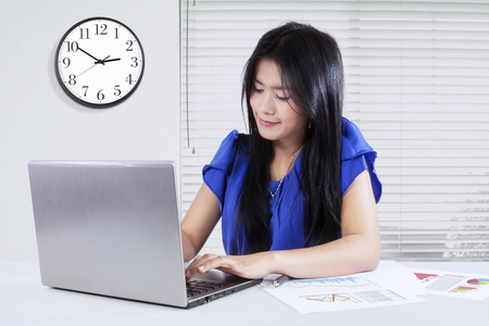 time table: Female entrepreneur working with paperwork while using laptop computer in the office