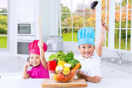 asian boy: Portrait of cheerful cute children ready to cook with fresh vegetables in kitchen at autumn season