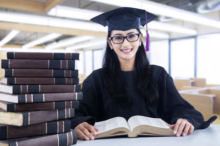 Asian female graduate is reading books in the library