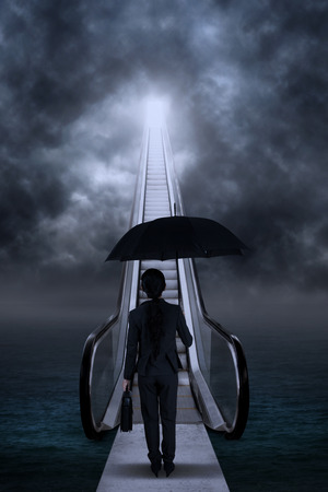 bad weather: Young businesswoman standing by the escalator on bad weather