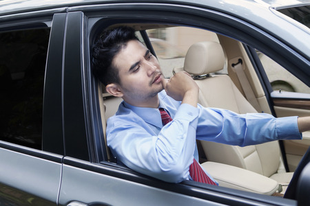 Thoughtful male worker driving a car while wearing formal suit and looks thinking something Banco de Imagens