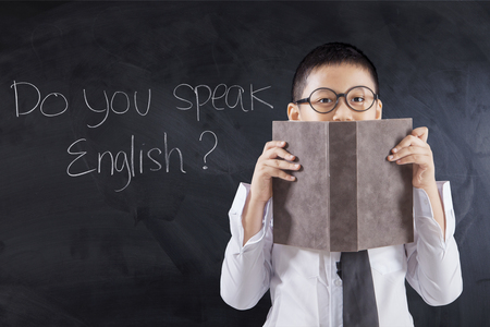 Photo of a little boy holding a book to cover his face with text Do You Speak English on the chalkboard Stock Photo