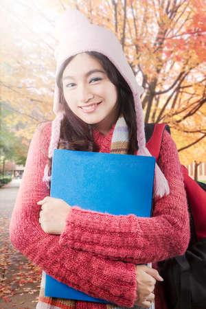 carpeta: Linda estudiante de escuela secundaria que lleva el bolso y la carpeta y sonriendo mientras llevaba suéter del parque en otoño Foto de archivo