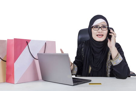 complaining: Muslim woman looks disappointed after shopping online and complaining by phone with laptop and shopping bags on the table Stock Photo