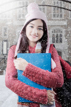 school yard: Photo of a beautiful teenage student smiling at the camera while wearing sweater with snowfall at school yard Stock Photo