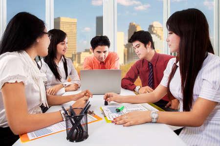 jovenes empresarios: Grupo de cinco jóvenes empresarios que se sientan en la oficina mientras se discute en conjunto con el ordenador portátil Foto de archivo