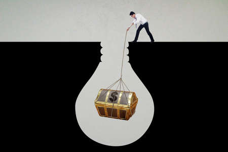 pulling rope: Image of a young businessman pulling a treasure chest with a rope