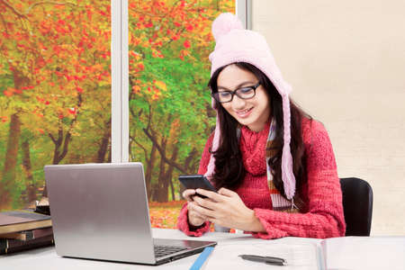 learning computer: Female learner studying at home while wearing sweater and using mobile phone with autumn background on the window