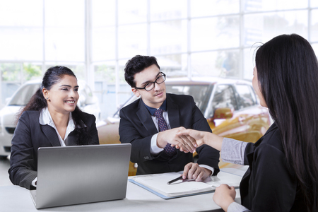 buyer: Portrait of two car seller smiling and shaking hands with their buyer in the showroom Stock Photo