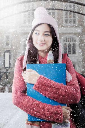 school yard: Beautiful schoolgirl wearing sweater and holding a folder with snowfall at school yard