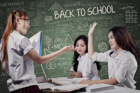 enquire: Portrait of female student raise hand and enquire a question on her friend in the class Stock Photo