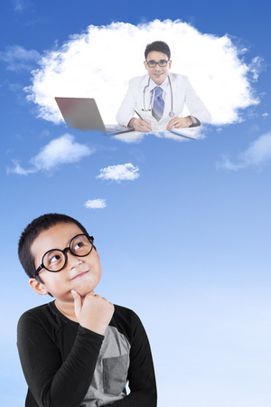 imagines: Portrait of a little boy wearing glasses and imagines a young doctor on a thought bubble Stock Photo