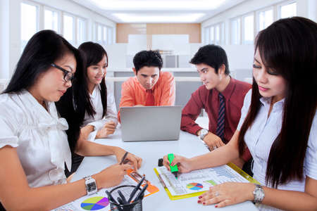 jovenes emprendedores: Grupo de jóvenes empresarios discutiendo en la sala de oficina con documentos y un ordenador portátil sobre la mesa Foto de archivo