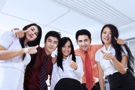 young group: Group of young business people showing thumbs up in the office while smiling at the camera Stock Photo