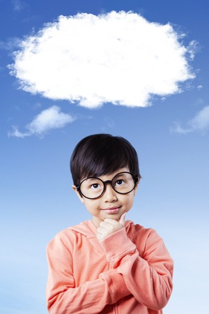 niños inteligentes: Portrait of a cute little girl wearing glasses and thinking under white cloud