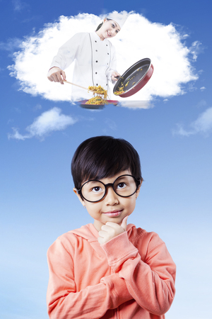 Pretty little girl wearing glasses and imagines a female chef cooking food on the thought bubble Stock Photo