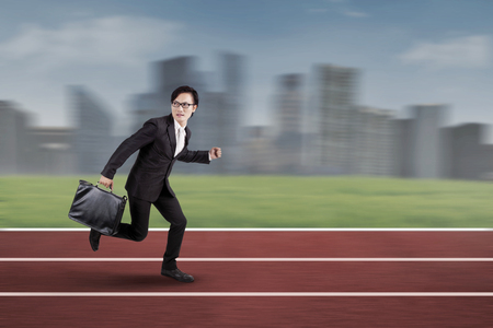 racing track: Young businessman carrying a briefcase and running on the track racing