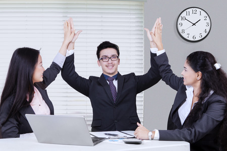businessman in office: Portrait of three multi ethnic successful entrepreneurs celebrating their winning by raising arms up together in the office