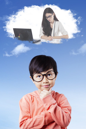 Beautiful little girl wearing glasses and imagines a businesswoman working with laptop on the thought bubble