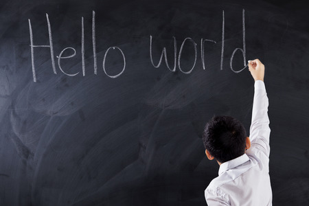 kids writing: Image of a male primary school student writes text Hello World on the chalkboard, shot in the class Stock Photo