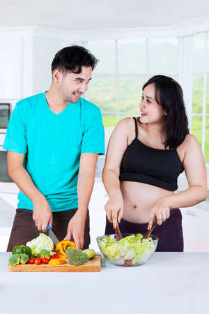 Beautiful pregnant woman and her husband preparing vegetable salad together in kitchen at home Stock Photo