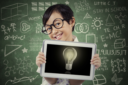 brilliant: Little schoolgirl wearing glasses and showing lightbulb on the digital tablet screen with doodles on the chalkboard Stock Photo