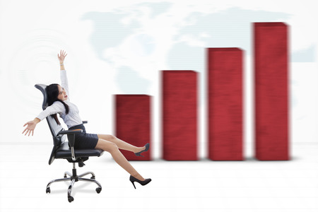 arms on chair: Cheerful young businesswoman sitting on the office chair and fast moving with growing financial chart