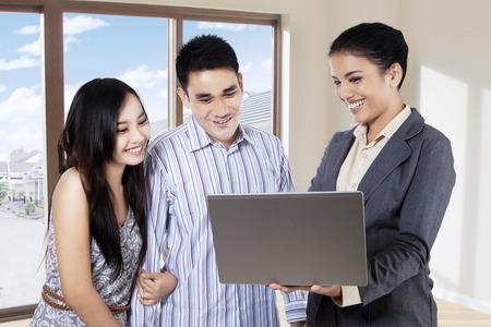 agente immobiliare femminile che mostra nuova casa a coppia con un computer portatile all'interno della nuova casa Archivio Fotografico