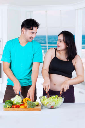 Portrait of Asian man and his wife preparing healthy food together in the kitchen at home