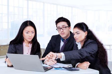 empleados trabajando: Tres empleados de múltiples étnicas que trabajan en la oficina mientras se discute plan de negocios con ordenador portátil en el escritorio Foto de archivo