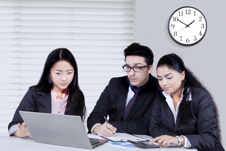 group strategy: Group of multi ethnic business partner using laptop in the office while working together to make a plan and strategy