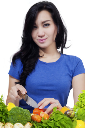young knife: Pretty young woman cutting fresh vegetables with a knife while smiling at the camera, isolated on white background