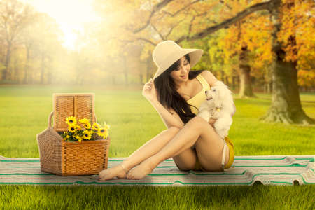 maltese dog: Portrait of beautiful young woman sitting on mat at the autumn park while holding her puppy
