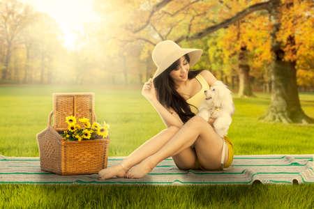 gente sentada: Retrato de la mujer hermosa joven que se sienta en la estera en el parque del otoño mientras que sostiene su perrito
