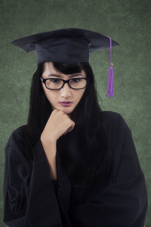 academic robe: Portrait of beautiful female learner standing in the classroom while wearing graduation gown and look at the camera