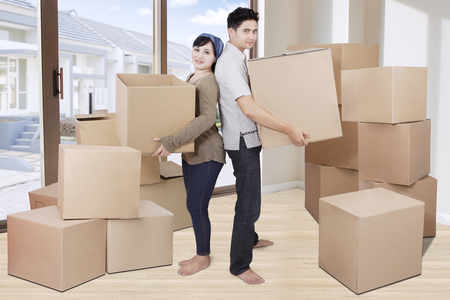 Photo of two young couple lifting cardboards in their new house while smiling at the camera