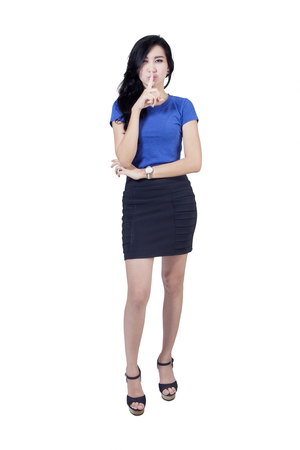 noiseless: Full length of beautiful woman standing in the studio while making a silence gesture, isolated on white background