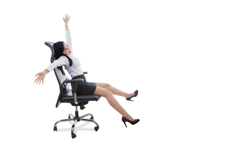 asian businesswoman: Photo of happy female entrepreneur celebrating her success while sitting on the office chair and raise hands