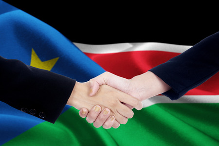 Picture of a negotiation handshake with two worker closing a deal and shaking hands in front of a national flag of South Sudan