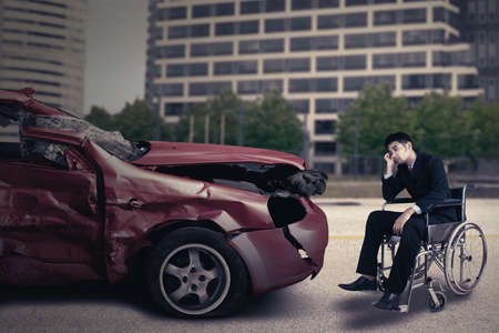 damaged car: Portrait of a disabled person sitting on wheelchair in front of a damaged car and looks sad Stock Photo