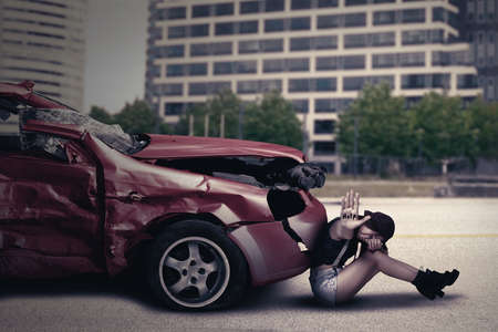dangerous: Image of a teenage girl sitting in front of a damaged car while showing Help word Stock Photo