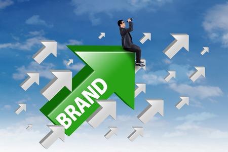젊은 사업가 브랜드 작업 상향 화살표에 앉아 쌍 안 하늘을보고 스톡 콘텐츠