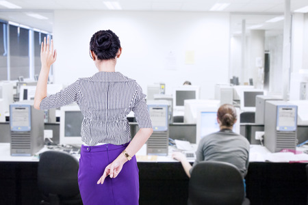 Businesswoman making oath but telling lies at the same time in the office Stock Photo
