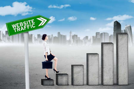 upward graph: Female worker walking on the upward graph with text of website traffic on the signboard Stock Photo